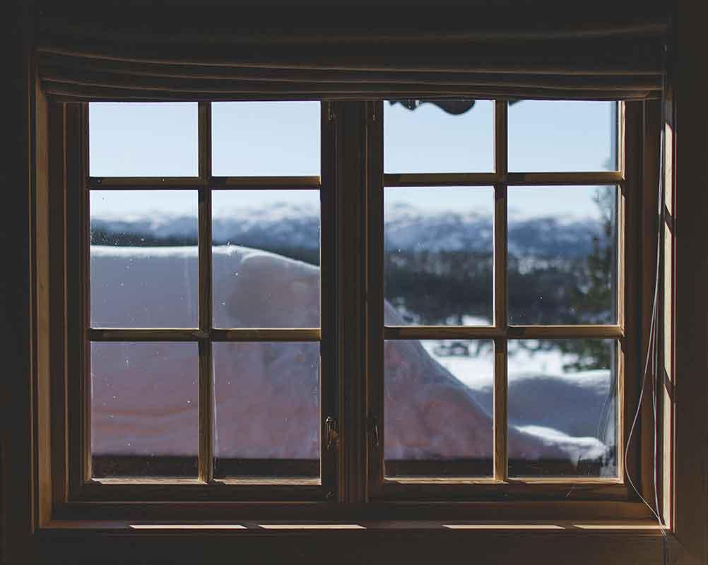 Ventana de madera con vista a paisaje con nieve